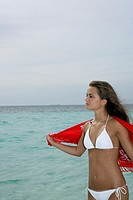 Young girl wearing bikini, standing at the beach