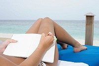 Young girl lying at deck chair, writing holiday diary