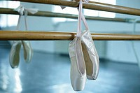 Ballet shoes hanging over a ballet bare
