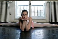 A female ballet dancer doing the splits on the floor