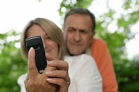 Mature couple taking a photo by a mobile phone