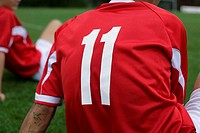 Soccer player wears number 11 sitting on grass