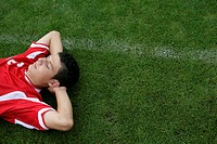 Soccer player with closed eyes lying on grass