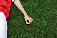 Soccer player lying on the grass