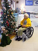 Senior female sits in a wheelchair next to a christmas tree while rehabilitating from a fall in a nursing home