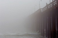 Man on pier in heavy fog. Ventura, California, USA