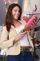 Low angle view of a young woman holding a shoe in a shoe store