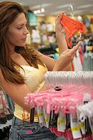 Side profile of a young woman looking at the price tag of underwear in a clothing store