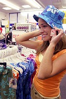 Side profile of a young woman trying on a hat in a clothing store