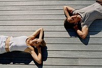 High angle view of a young couple lying on wooden planks