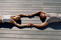 High angle view of a young couple lying on wooden planks holding hands (thumbnail)