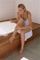 High angle view of a young woman applying shaving cream on her legs