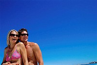 Low angle view of a young couple smiling on the beach