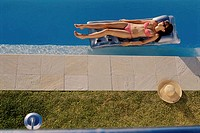 High angle view of a young woman lying on a pool raft