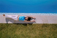 High angle view of a young woman lying at the poolside