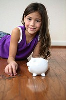 Portrait of a girl lying on the floor with a piggy bank in front of her
