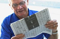 Close-up of a senior man reading a newspaper