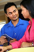 Side profile of a young woman with a young man holding a calculator