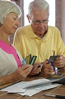 Close-up of a senior couple destroying credit cards