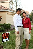 Young couple standing on the lawn of a house smiling