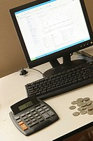 Close-up of a desktop pc with a calculator and coins on a table