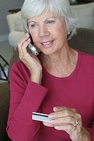 Senior woman talking on a mobile phone holding a credit card