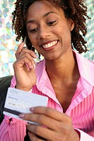 Young woman talking on a mobile phone holding a credit card