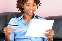 Close-up of a young woman holding a credit card reading a bill