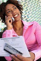 Close-up of a young woman holding a bill using a mobile phone