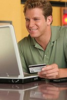 Young man using a laptop holding a credit card