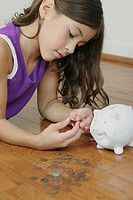 Side profile of a girl lying on the floor counting coins
