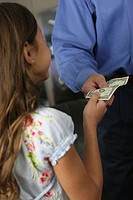Side profile of a daughter taking a dollar bill from her father
