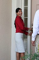 Side profile of a young woman unlocking a door