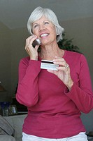 Low angle view of a senior woman talking on a mobile phone holding a credit card