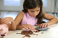 High angle view of a girl counting coins