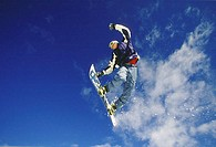 Teenager performing stunt on snowboard