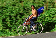 Young man riding bicycle carrying surfboard
