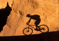 Shadow of person mountain biking