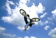 Young man performing stunt on bicycle (thumbnail)