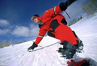 Young adult man snowboarding downhill (thumbnail)