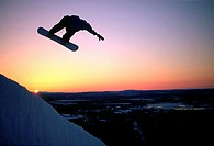 Silhouette of person performing stunt on snowboard