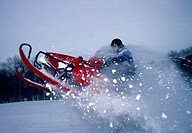 Side profile of a man riding a snowmobile