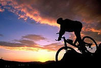 Silhouette of a person mountain biking