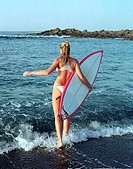 Rear view of a young woman carrying a surfboard on the beach