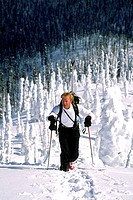 High angle view of a mid adult man walking with skis in backpack