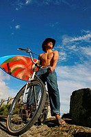 Low angle view of a young man on a bicycle with a surfboard under one arm