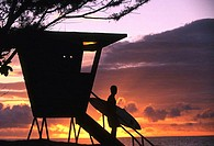 Silhouette of a young man with a surfboard on the steps of a lifeguard hut