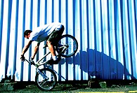 Side profile of a young man performing stunts on a bicycle
