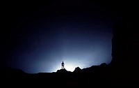 Silhouette of a person standing in the opening to a cave in Xingwen National Geopark, China