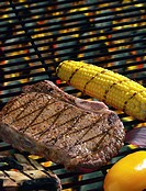 Close-up of a piece of meat and corn on the cob cooking on a grill